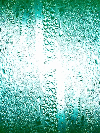 Greenish turquoise backdrop of glass surface with water drops textures photo