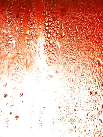 watery: Redish orange soda background full of liquid drops
