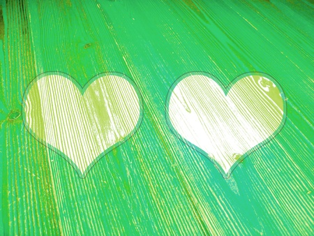 romaticism: Fresh juvenile green couple of hearts on old wood background Stock Photo