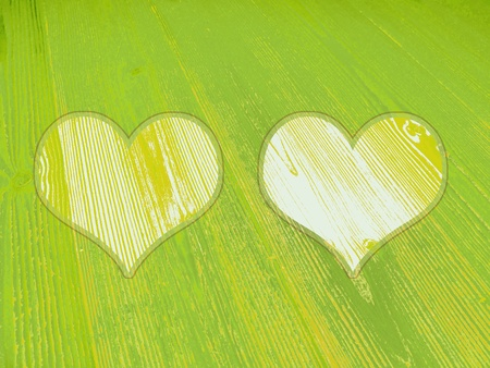 romaticism: Light green romantic background with a couple of hearts on old wood