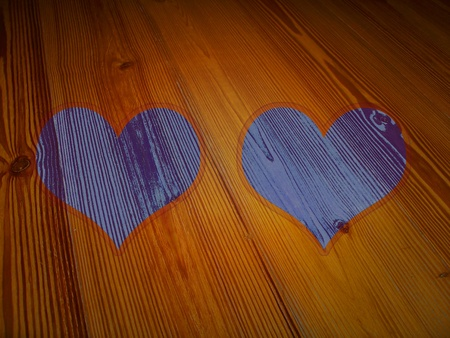 romaticism: Couple of blueish violet hearts as frames on vintage wood