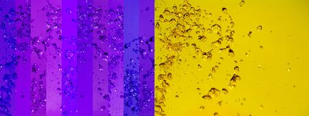 colortherapy: Color alchemy in a large horizontal background with intense beautiful contrast of yellow and violet of colored water with drops