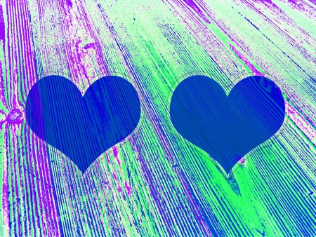 Two blue hearts on fosforescent juvenile striped old wood colorful background photo