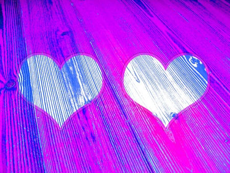 Couple of hearts on luminous fluorescent pink and blue background photo