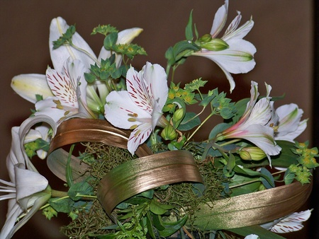 Elegant bouquet of a wedding with white lilies on its green and gold leaves photo