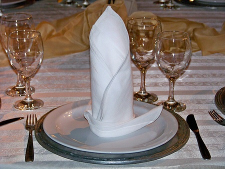 bright center: Place for one on an elegant wedding dinner table in white, silver and gold