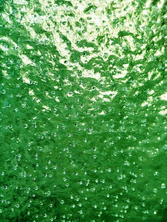 Green brilliant background of frozen water with dots of air bubbles in it Stock Photo - 12126765