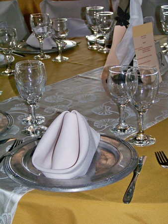 Elegant unique celebration lunch table in golden yellow, silver of pewter plates and white  photo