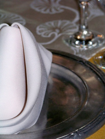 Elegant close up to a celebration table detail of a white cloth napkin on a metallic pewter silver plate photo