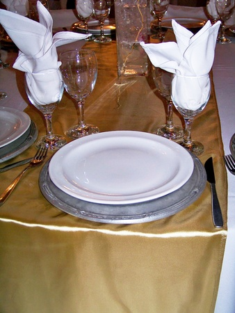 Shinny brilliant gold fabric tablecloth on an elegant luxury dinner table service in golden, silver and white photo