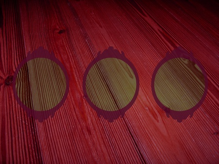 Old pinkish dark red wood background with three circular empty frames for pictures Stock Photo - 12126696