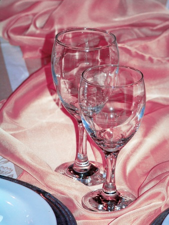 Two glasses on pink silk tablecloth for Valentine couple party dinner photo