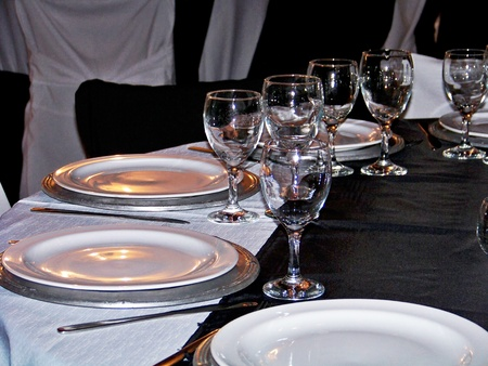 White, black and silver elegant restaurant dinner table for a group photo