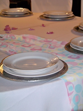Elegant birthday party tableware in light colors with silver pewter and white ceramic plates