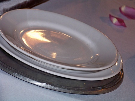 Three plates on a table with pink roses petals, one silver of pewter metal and two white of ceramic