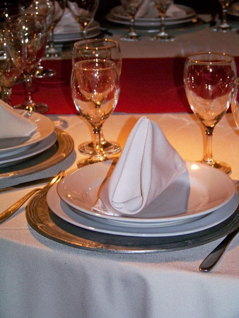 Complete place on a romantic festive table in red white and silver with warm light photo