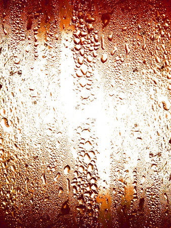 redish: Background of light with little drops on a beverage glass in redish brown