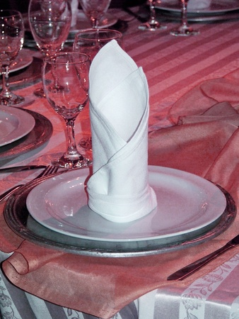 Vertical elegant tubed cloth napkin over ceramic and pewter plates on a calid beautiful table in pink with warm lights photo