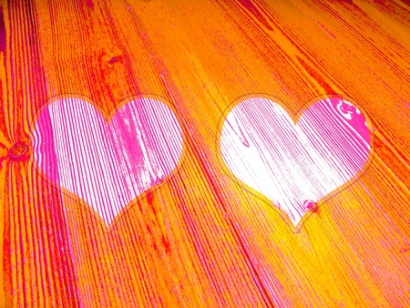 romaticism: Warm background with couple of hearts on old striped wood in orange tones