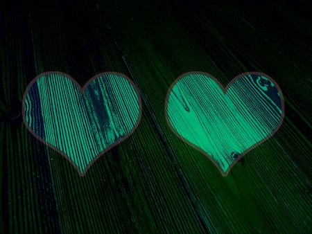 romaticism: Couple of luminous green hearts in the darkness of old wood background