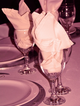 Glasses with napkins over restaurant table in yellowish sepia and purple photo