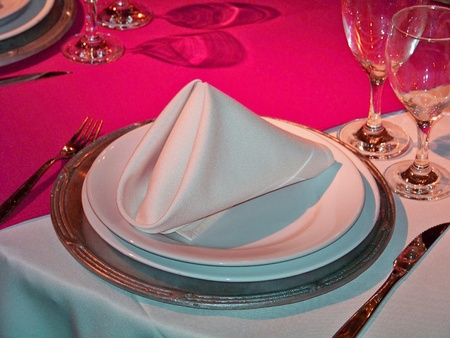 An elegant place in a restaurant table in silver, white and intense magenta pink in metal, ceramic and glass photo