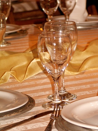 Elegance in festive restaurant table, glasses surrounded by white, golden yellow and silver Stock Photo - 12623447