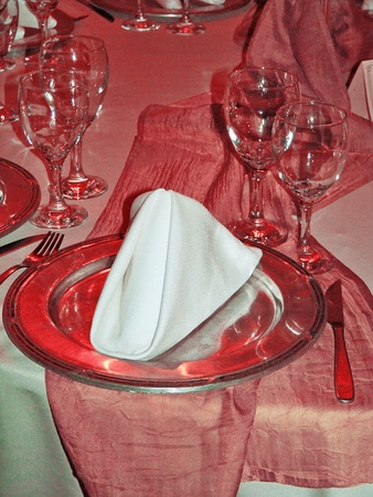 Warm elegant sophisticated restaurant festive table in pinkish orange, silver and white under a red light photo