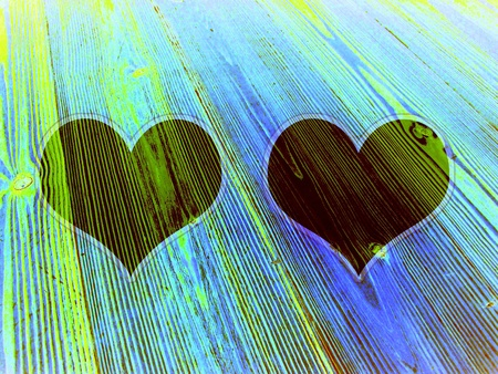 romaticism: Two dark hearts on old wood in green and blue