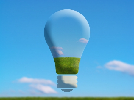 Giant bulb of light over a green field with clear blue sky photo