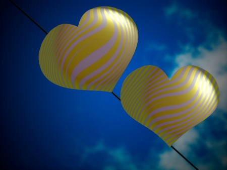Brilliant yellow and silver couple of hearts balloons under blue sky photo