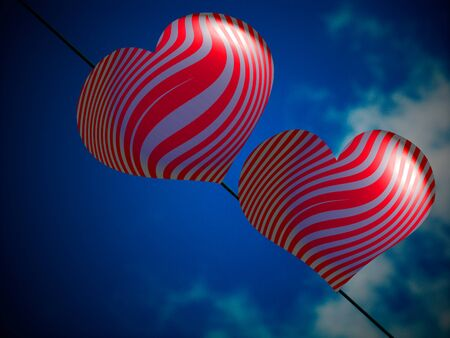 Couple of red heart shaped ballons on a dope under the blue sky photo