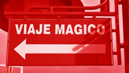 typographies: Magis trip, viaje magico, street signal in red with an arrow