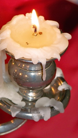 White burning melting candle on vintage silver candlestick over red photo