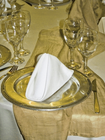 Golden tableware and table cloth of a wedding dinner service photo