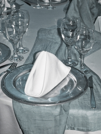 Elegant silver table place with pewter plate and white cloth napkin close up photo