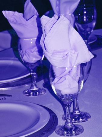 Blue light on celebration table close-up with napkins in wine glasses  photo