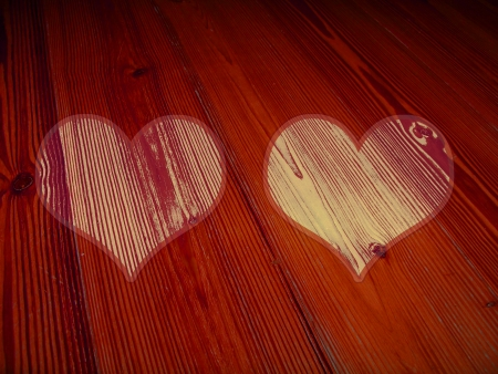 romaticism: Couple of hearts on red wood for christmas postcard
