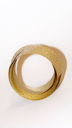 metalized: Circular golden christmas ribbon isolated on white with copyspace