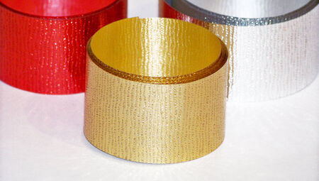 Christmas ribbons of three colors gold silver and red on white photo