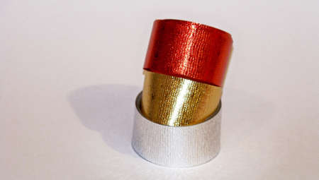 metalized: X-mas ribbons stack in red golden and silver on white