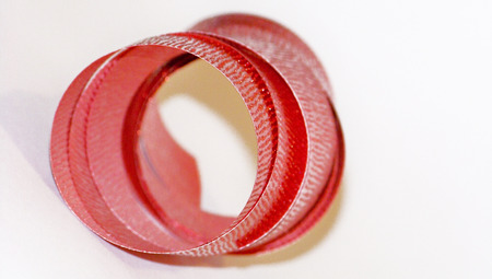 metalized: Red christmas ribbon spiral close up isolated on white