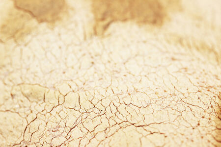 sooth: Broken dried clay mask texture on skin background closeup