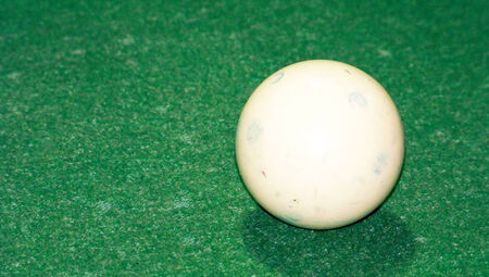 White billiard ball on old green cloth texture background photo
