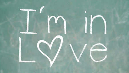 i am: I am in love concept on school blackboard green background