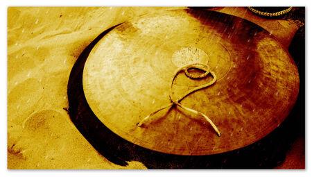Golden Tibetan cymbal on sand Stock Photo - 27388168