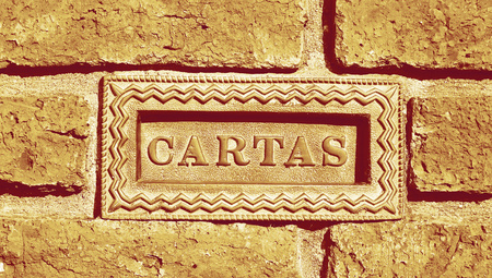goldish: Mail box with cartas spanish word on wall background of bricks Stock Photo