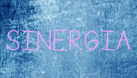 Sinergy spanish word on chalk board blue background