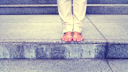 Woman foot without shoes in a city photo