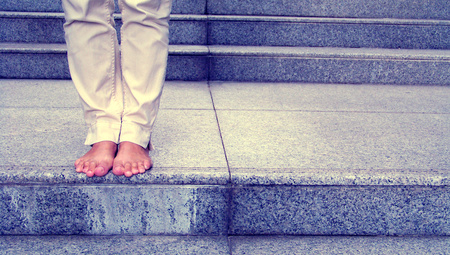 Barefoot female standing on stair step of marbel stone photo